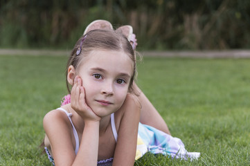 portrait of young girl laying and posing in grass