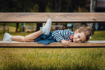 Pleasure little girl lying on bench in a park