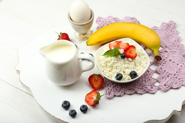 Delicious breakfast with cottage cheese, milk and fruits