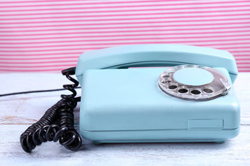 Retro turquoise telephone on wooden table, on color background