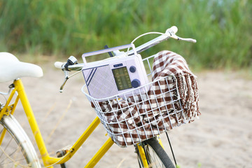 Bicycle with retro radio in meadow during sunset