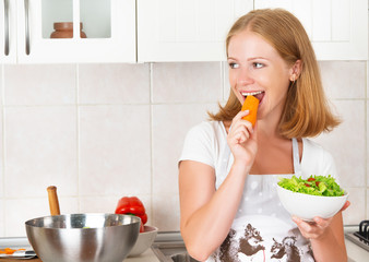 young happy woman eats vegetable salad on kitchen
