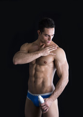 Muscular fit man applying ointment to his shoulder