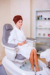 Beautiful girl in a beauty salon doing a pedicure