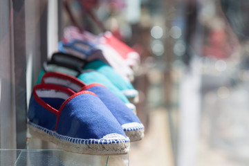 row of colorful espadrilles in front of shop