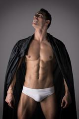 Naked man in briefs posing as a vampire