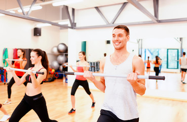 group of smiling people working out with barbells