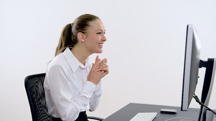 Young beautiful businesswoman typing on a computer and is happy