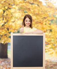 happy little girl with blank blackboard
