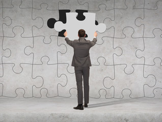businessman in suit setting piece of puzzle