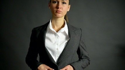 Charming woman crosses her arms on a grey background.