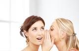 two smiling women whispering gossip