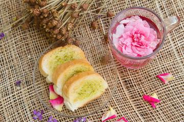 Rose tea and homemade garlic bread on table in the garden