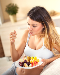 Pregnant woman sitting in her living room and eating fruits
