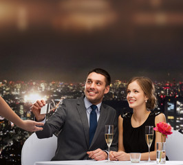 smiling couple paying for dinner with credit card