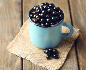 Ripe blackcurrants in mug