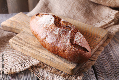 canvas print picture Fresh bread on wooden table, close up