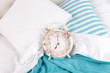 Metal clock on blue pillows on a big white bed