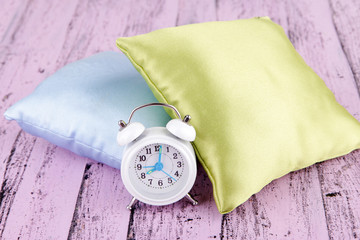Plastic clock on a silk pillows on wooden background