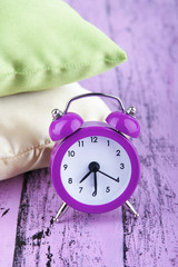 Plastic clock on a silk pillows on wooden purple background