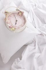 Metal clock on pillows on a big white bed