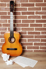 Guitar on the floor on brick wall background