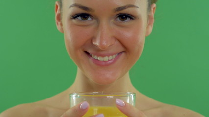 young beautiful woman drinking orange juice on the green screen