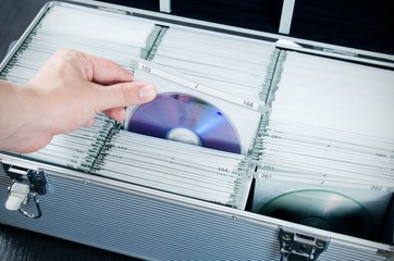 Hand pulls disc from aluminum carrying CD-DVD case