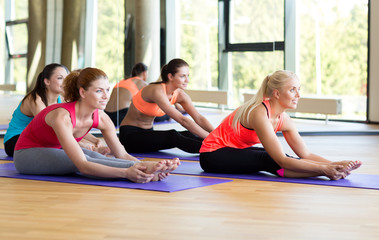 group of smiling women stretching in gym