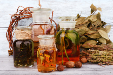 Bottles of herbal tincture and dried leaves on wooden