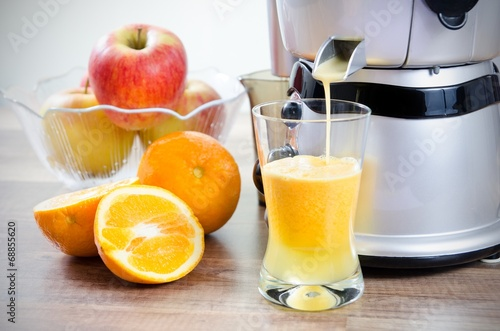 Juicer and orange juice. Fruits in background