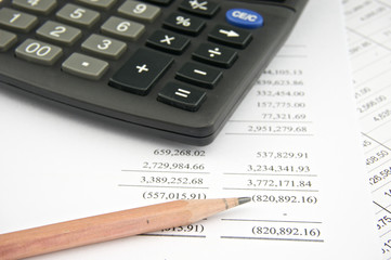 Statements of income with pencil and black calculator