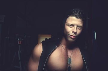 Handsome guy posing in hood. Bodybuilder