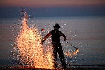 Sparks of spinning poi in fire show