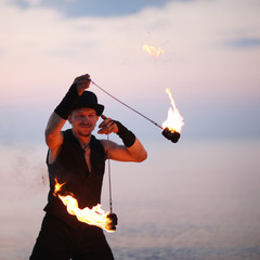 Close up of a man spinning fire poi