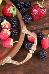 Different berries and fruits on tray on wooden table close-up