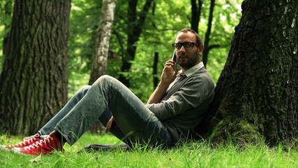 Young handsome man talking on cellphone, relaxing in park