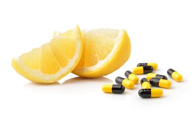 Slice of lemon fruit and pills capsules isolated on white backgr
