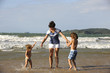 Happy mother and daughters having fun on the beach