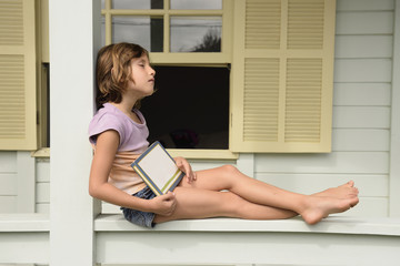 Child reading a book on the balcony.