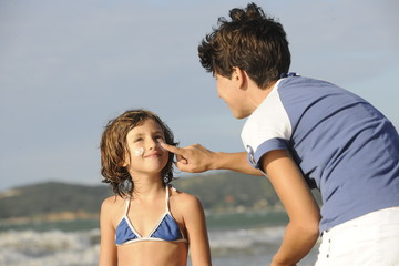 Mother applying sunscreen to daughter at beach.