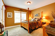 Cozy bedroom with carved wood bed and high poles