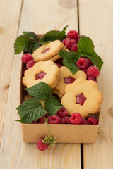 Homemade cookies with raspberry jam and fresh raspberries