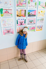 Girl near wall with children drawings