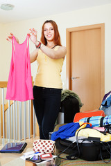 woman adding clothes into suitcases
