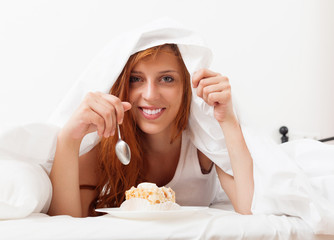 Smiling girl eating biscuit in  bed