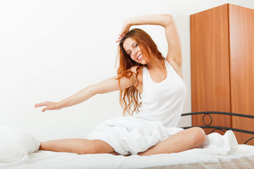 girl in a white shirt lying on the sheets in the bed at home