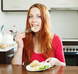woman eating potatoes at home