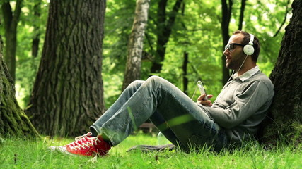 Young man listen to music on smartphone in the park