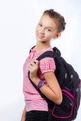 Beautiful girl with school backpack on a gray background